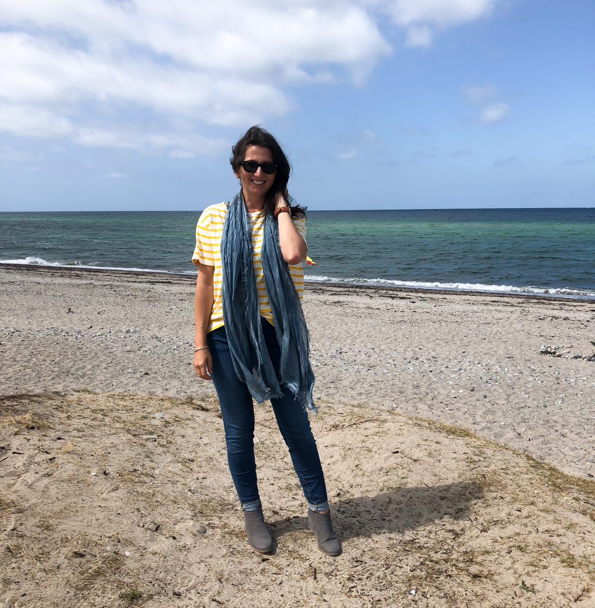 Erin stands on the beach along the Baltic Sea wearing a long scarf.