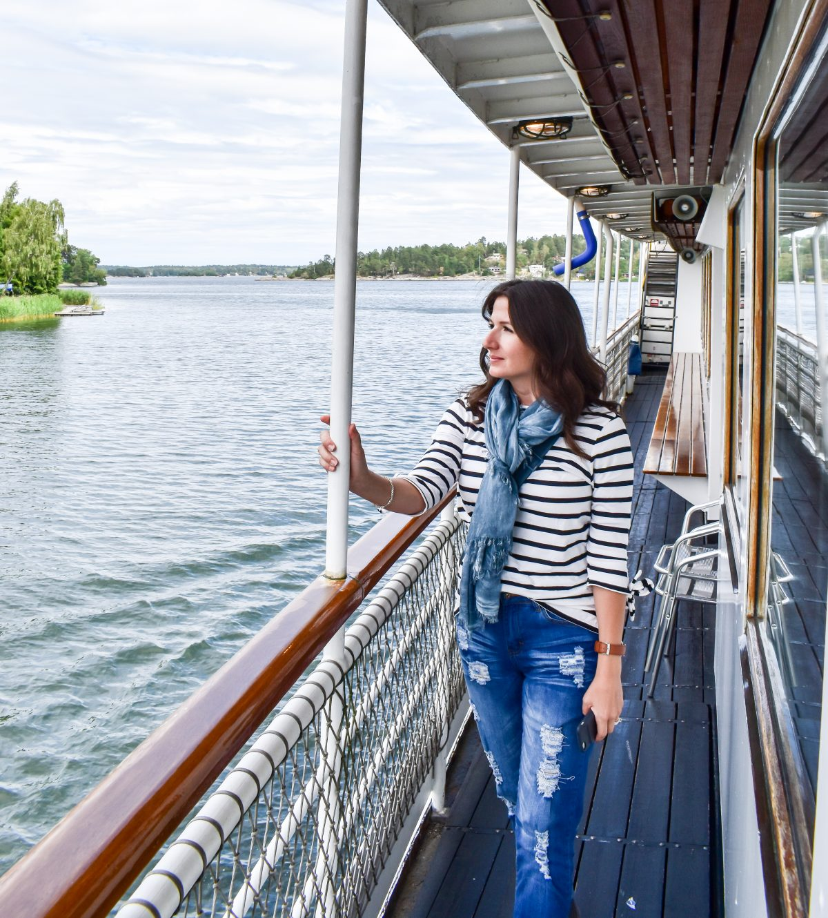 Erin wears a nautical striped top and gazes across the water on a canal cruise in Sweden.