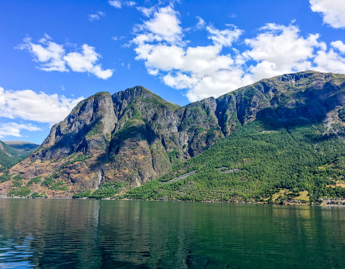 A lush green fjord rises out of the water in Norway