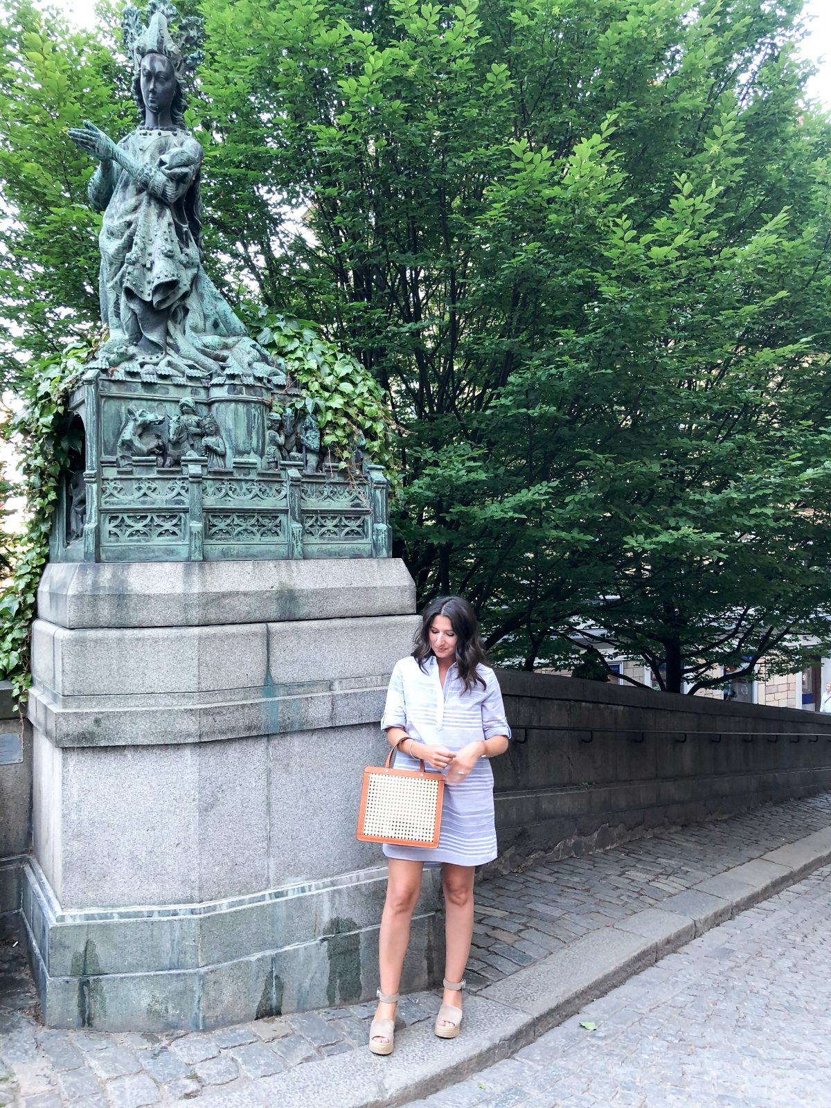 Erin wears a tunic dress with a Palmgrens rattan collection bag in Stockholm Sweden.