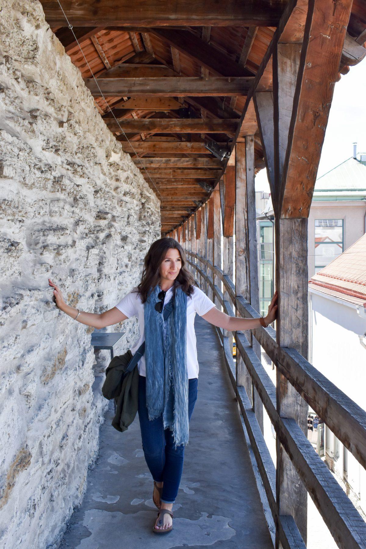 Erin walks the medieval wall in Tallinn Estonia wearing her favorite travel wardrobe essential, a long scarf.