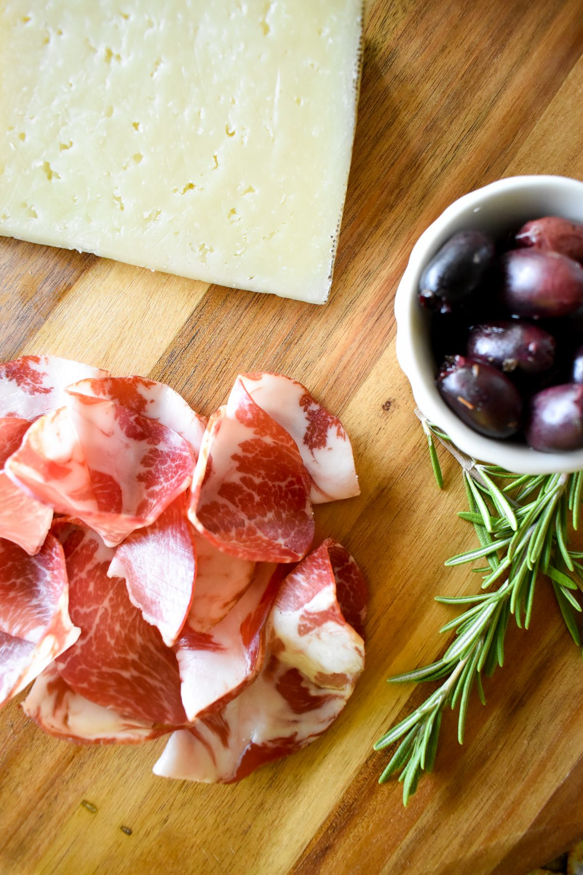 A close up of Erin's charcuterie board showing detail of coppa, manchego, and olives.