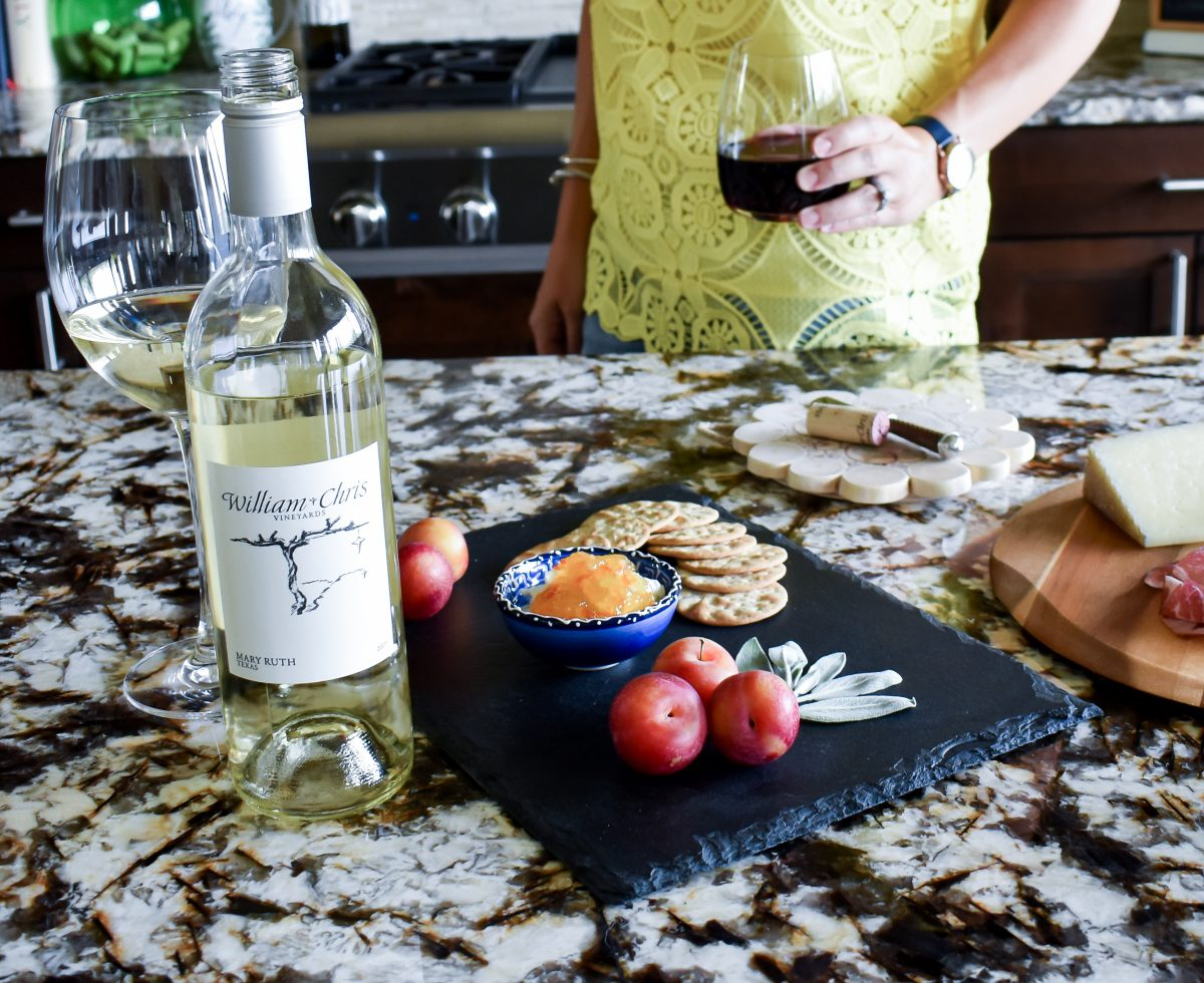 A cheese board with cherry plums, goat cheese, and pepper crackers with Mary Ruth white wine from William Chris Vineyards.