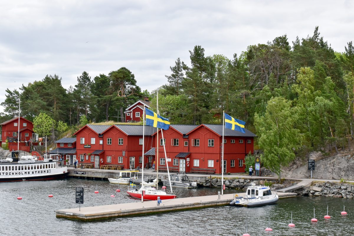 A view of red wooden buildings and Swedish flags along the archipelago